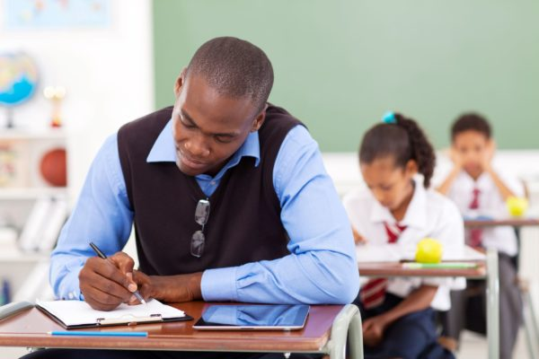 18417343 - african american primary school teacher preparing a lesson in classroom