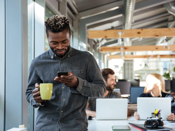 Image of smiling young african man standing in office chatting by phone drinking coffee. Looking aside.